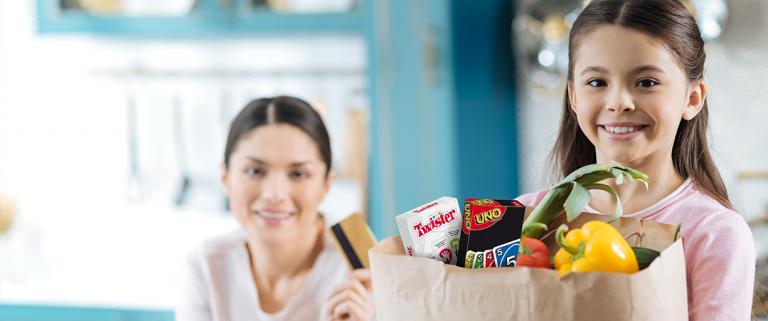 Frau mit Kind, welches Einkaufstüte in der Hand hält und Pocket Game Twister sowie Uno schauen heraus.